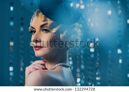 Elegant blond retro woman with beautiful hairdo and red lipstick wearing hat with veil - stock photo