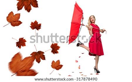 Elegant blonde holding umbrella against autumn leaves pattern - stock photo