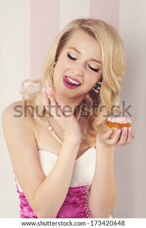 Elegant blonde woman eating cream from muffin