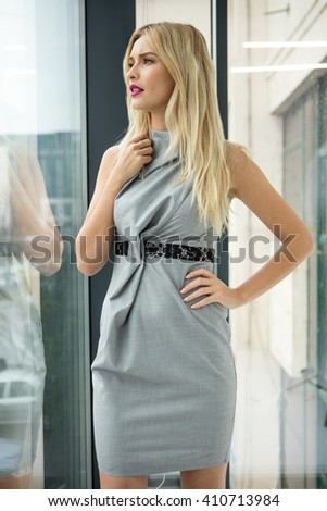 elegant blonde women standing next to an office building window - stock photo