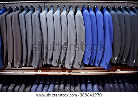 Elegant blue and gray suits on hangers are seen in a suit store - stock photo