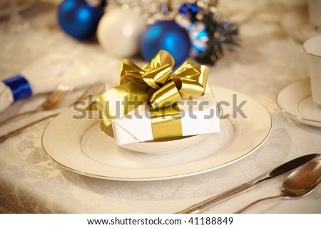 Elegant blue and white Christmas table setting with gold ribbon gift - stock photo