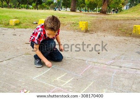 Elegant boy drawing hopscotch with chalk on the ground - stock photo