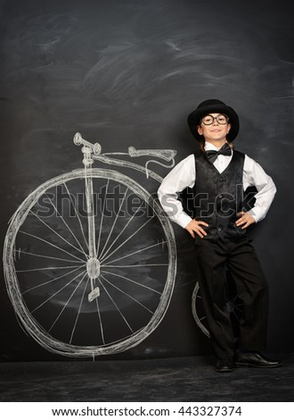 Elegant boy in a suit, bowler hat and glasses stands by a painted retro bicycle. Old Europe style, England. Little gentleman. Kid's fashion. - stock photo