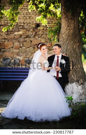 Elegant bride and groom posing together outdoors on a wedding day. Groom and Bride in a park. wedding dress. Bridal wedding bouquet of flowers