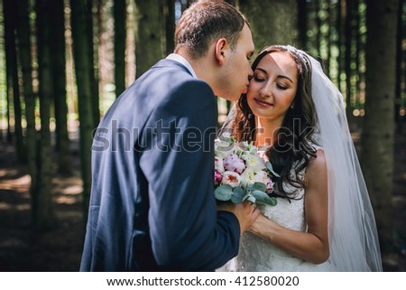 Elegant bride and groom posing together outdoors on a wedding day. Kiss