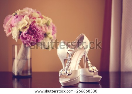 Elegant bride's shoes with a peonies bouquet - stock photo