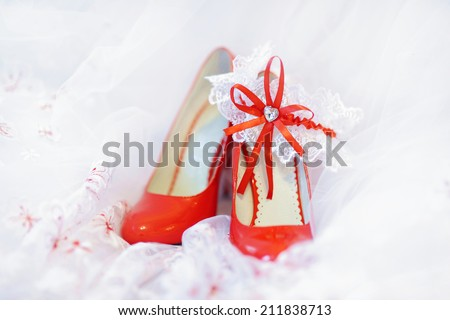 Elegant bright red bridal shoes and a white garter