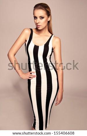 Elegant brunette in black and white dress posing in the studio  - stock photo