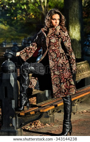 Elegant brunette model wearing coat and high heel boots posing at Central Park New York location for fall fashion photo shoot. - stock photo