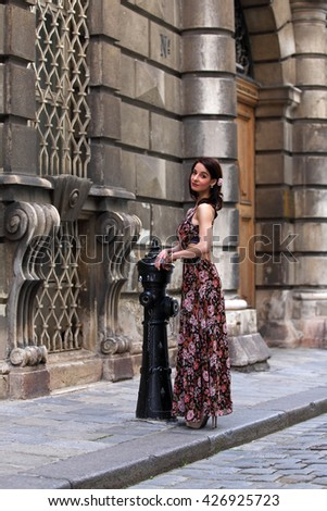 Elegant brunette woman in front of a baroque palace