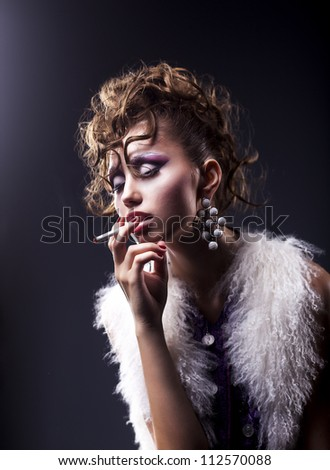 Elegant brunette woman smoking a cigarette on black background - bad habits - stock photo