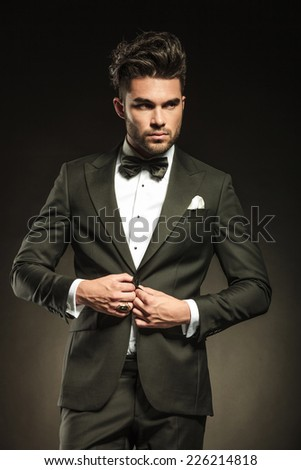 Elegant business man arranging his tuxedo while looking away from the camera. - stock photo