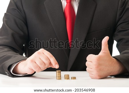Elegant business man counting piles of coins and showing the international OK sign - stock photo