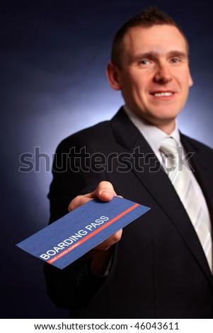 Elegant business man holding a boarding pass - stock photo
