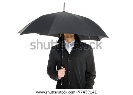 elegant business man in a raincoat standing under an umbrella. - stock photo