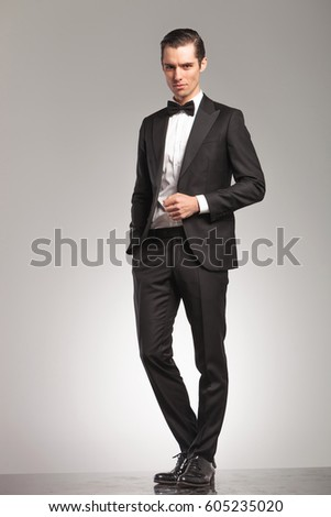 elegant business man in tuxedo standing with open coat on grey studio background
