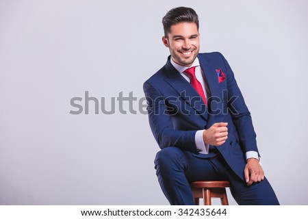 elegant business man leaning while sitting and smiling in studio  - stock photo