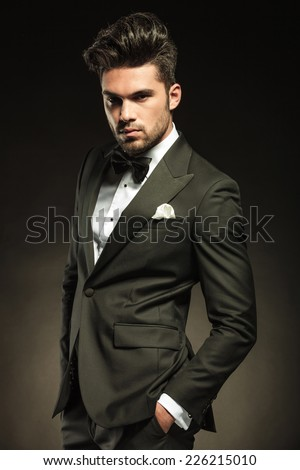 Elegant business man looking at the camera while holding his hands in pocket. On black studio background. - stock photo