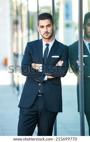 elegant business man standing next to an office building