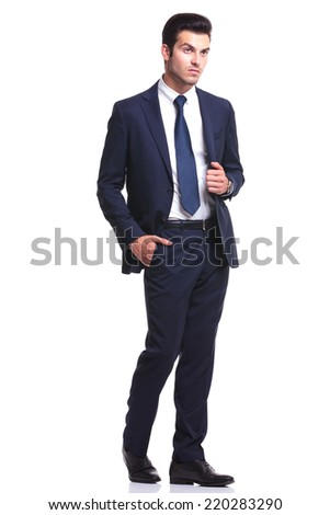 Elegant business man walking on white studio background, with one hand in his pocket and the other one on his jacket, looking away from the camera - stock photo