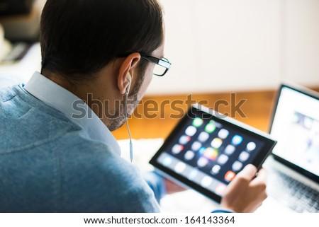 elegant business multitasking multimedia man using devices at home - stock photo