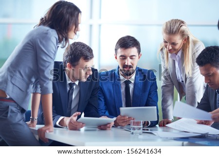 Elegant business partners interacting and planning work at meeting - stock photo