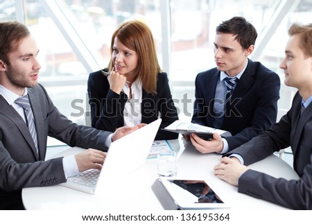 Elegant business partners listening to colleague at meeting