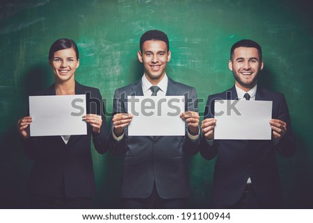 Elegant business partners with blank papers looking at camera on green background - stock photo