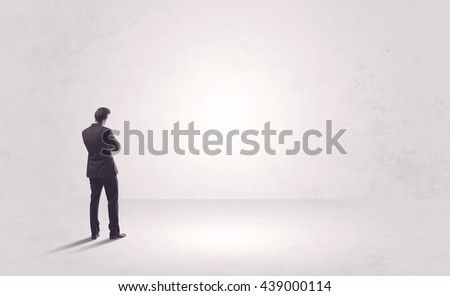 Elegant business person standing with his back looking at big empty white space concept - stock photo