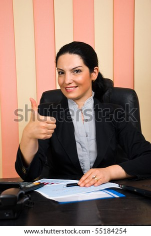 Elegant business woman sitting on chair at desktop in her office and giving thumbs up