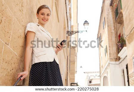 Elegant business woman standing in a classic city with textured stone buildings and walls, holding a high technology smartphone in her hand, smiling at the camera outdoors. People and technology.