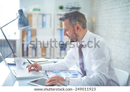 Elegant businessman analyzing data in office