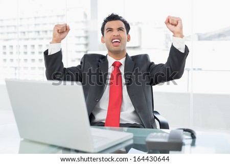 Elegant businessman cheering with clenched fists in front of laptop at office desk
