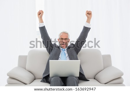 Elegant businessman cheering with clenched fists in front of laptop on sofa in living room at home