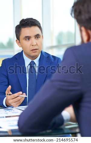 Elegant businessman communicating with his colleague at meeting - stock photo