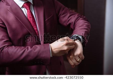 Elegant businessman correcting his cclocks and sleeve. Mans acce - stock photo