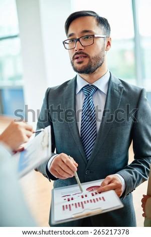 Elegant businessman explaining data to colleagues at meeting - stock photo