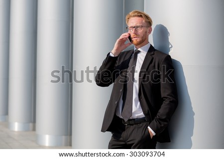 Elegant businessman in black suit speaking over mobile phone. Red-haired man in glasses discussing several isuues and problems. - stock photo