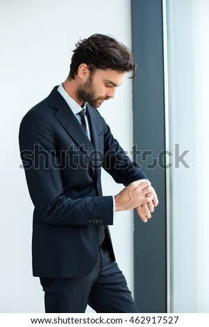 elegant businessman in suit standing next to a big window from an office building and checking his watch