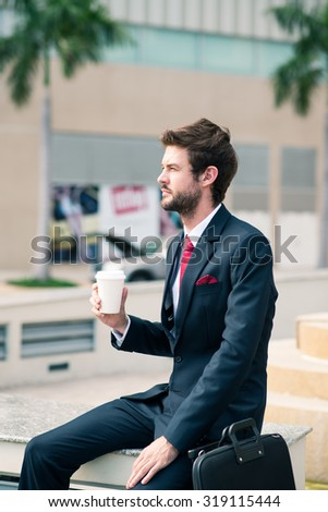Elegant businessman sitting outdoors and enjoying his morning coffee