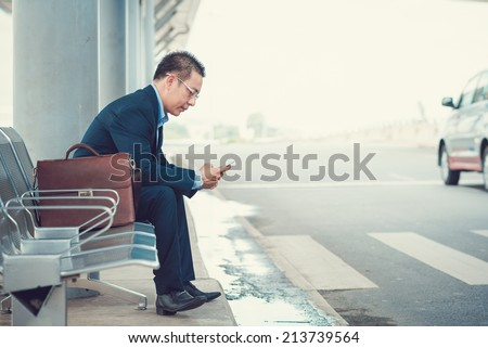 Elegant businessman texting while sitting at the bus stop in the airport - stock photo