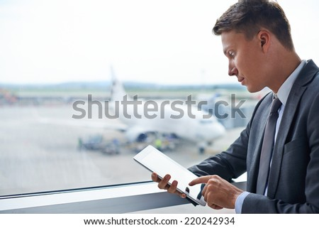 Elegant businessman touching screen of digital tablet in airport - stock photo