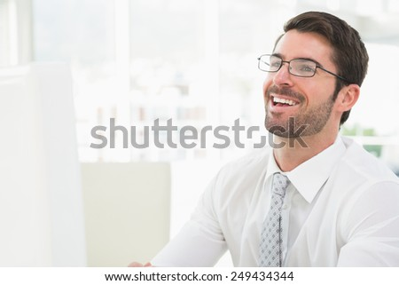 Elegant businessman with glasses laughing in his office - stock photo