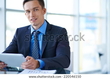 Elegant businessman with touchpad looking at camera - stock photo