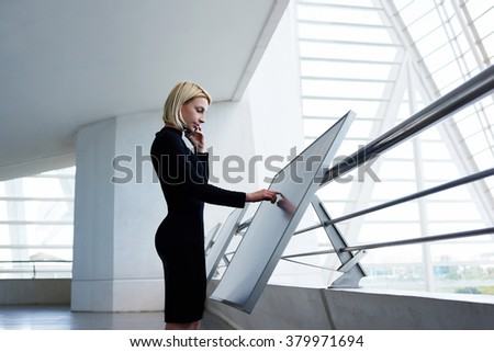 Elegant businesswoman consulting via cell telephone about report on modern interactive display, young female talking on mobile phone and using advanced technology while standing in office interior - stock photo