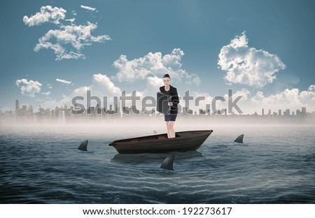 Elegant businesswoman in suit carrying briefcase against sharks circling a small boat in the sea