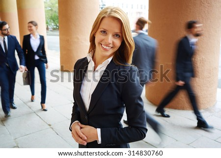 Elegant businesswoman looking at camera on background of walking people - stock photo