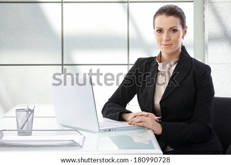 Elegant businesswoman sitting at desk, using laptop computer, looking at camera, smiling. - stock photo