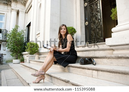 Elegant businesswoman sitting on a classic buildings steps taking notes in her agenda, smiling. - stock photo
